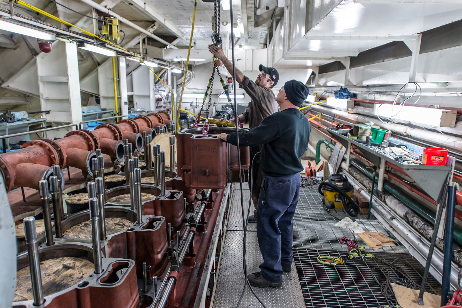 On the Edwin H. Gott, Michael Kolenda (foreground), Great Lakes Fleet engineer, and Aurel Carina, MaK service engineer, remove heads from the starboard main engine as it undergoes a complete overhaul, part of routine winter maintenance. Credit: Robert Welton
