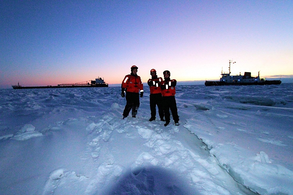 Chief Petty Officer Nick Gould, Petty Officer 1st Class Dwayne Matthews and Petty Officer 3rd Class Angelo Barnett stand on frozen Lake Huron with the motor vessel Capt. Henry Jackman and Coast Guard Cutter Bristol Bay in the background, Feb. 10, 2015. As part of Operation Coal Shovel, the crew of the Bristol Bay broke the Jackman free from the ice and assisted it northbound. Credit: U.S. Coast Guard photo by Chief Petty Officer Nick Gould