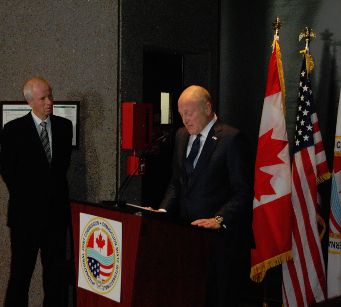 Heyman, at podium, speaks during IJC reception while Dion, at left, looks on. Credit: IJC files